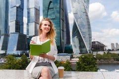 Junge hübsche Frau sitzende aganst Bürogebäude Lizenzfreie Stockfotos