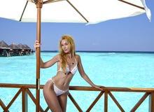 Junge hübsche Frau steht in Badeanzug auf Plattform am Landhaus auf Wasser, Malediven Stockfoto
