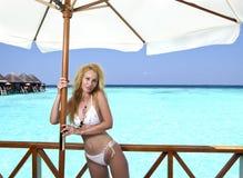 Junge hübsche Frau steht in Badeanzug auf Plattform am Landhaus auf Wasser, Malediven Lizenzfreies Stockfoto