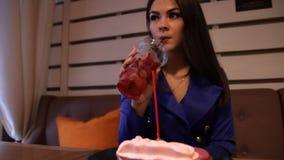 Junge hübsche Frau trinkt ein Auffrischungsgetränk, das in einem Café sitzt stock video footage