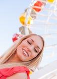 Junge hübsche Frau vor einem Riesenrad Stockfotografie