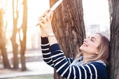 Junge hübsche Frau wirft beim Fotografieren auf Tablette für Bild des Sozialen Netzes während der Erholungszeit im Park, Holzkohl Lizenzfreie Stockbilder