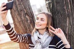 Junge hübsche Frau wirft beim Fotografieren am Handy für Bild des Sozialen Netzes während der Erholungszeit im Park auf Stockbilder
