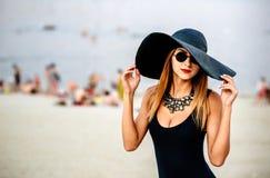 Junge hübsche Frauen auf dem Strand in der schwarzen Badebekleidung Stockfotografie