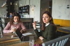 Junge hübsche Frauen, die mit Anmerkungen und Laptop im Café arbeiten Lizenzfreies Stockbild