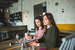 Junge hübsche Frauen, die mit Anmerkungen und Laptop im Café arbeiten Stockfotos
