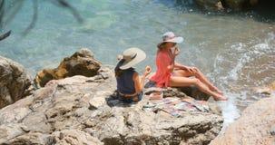 Junge hübsche Frauen im Badeanzug und in Vertuschung, die auf den Felsen nahe dem Meer sitzen stock video