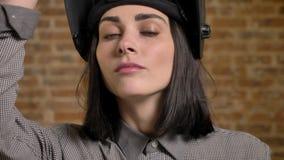 Junge hübsche Frauen mit dem kurzen braunen Haar, das die Kamera, ihren Sturzhelm anhebend, weiblicher Erbauer, Ziegelsteinhinter stock video