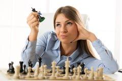 Junge hübsche Geschäftsfrau With Chessmen Stockfoto