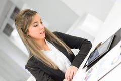Junge hübsche Geschäftsfrau mit Tablet-Computer im Büro lizenzfreie stockfotos