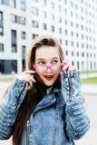 Junge hübsche Hippie-Studentin mit der Kaffeetasse, die das entzückende Lächeln, Lebensstilleutekonzept im Freien aufwirft Stockfotografie