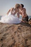 Junge hübsche Paare, die auf Felsen am Strand sitzen Stockfotos