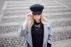 Junge, Hüfte und attraktives blondes Gehen um die Stadt, Mädchen in einem stilvollen Hut und ein grauer Mantel Zebrastreifen in d Lizenzfreie Stockfotos