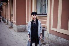 Junge, Hüfte und attraktives blondes Gehen um die Stadt, Mädchen in einem stilvollen Hut und ein grauer Mantel Lizenzfreie Stockfotos