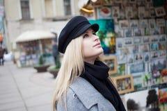 Junge, Hüfte und attraktives blondes Gehen um die Stadt, Mädchen in einem stilvollen Hut und ein grauer Mantel Stockbilder