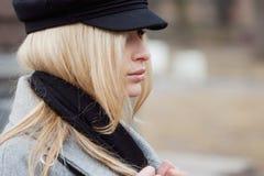 Junge, Hüfte und attraktives blondes Gehen um die Stadt, Mädchen in einem stilvollen Hut und ein grauer Mantel Stockfotografie