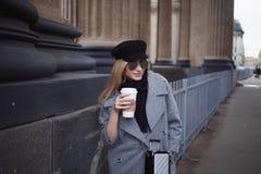 Junge, Hüfte und attraktives blondes Gehen um die Stadt mit Kaffee zum Mitnehmen, Mädchen in einem stilvollen Hut und ein grauer  Lizenzfreie Stockfotos