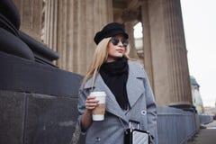 Junge, Hüfte und attraktives blondes Gehen um die Stadt mit Kaffee zum Mitnehmen, Mädchen in einem stilvollen Hut und ein grauer  Lizenzfreies Stockbild