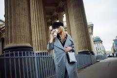 Junge, Hüfte und attraktives blondes Gehen um die Stadt mit Kaffee zum Mitnehmen, Mädchen in einem stilvollen Hut und ein grauer  Stockfoto