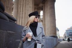 Junge, Hüfte und attraktives blondes Gehen um die Stadt mit Kaffee zum Mitnehmen, Mädchen in einem stilvollen Hut und ein grauer  Stockbild