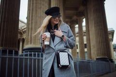 Junge, Hüfte und attraktives blondes Gehen um die Stadt mit Kaffee zum Mitnehmen, Mädchen in einem stilvollen Hut und ein grauer  Stockfotografie