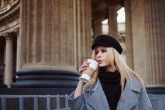 Junge, Hüfte und attraktives blondes Gehen um die Stadt mit Kaffee zum Mitnehmen, Mädchen in einem stilvollen Hut und ein grauer  Stockbilder
