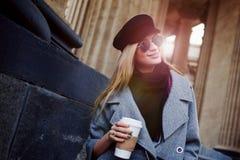 Junge, Hüfte und attraktives blondes Gehen um die Stadt mit Kaffee zum Mitnehmen, Mädchen in einem stilvollen Hut und ein grauer  Lizenzfreie Stockfotografie