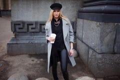 Junge, Hüfte und attraktives blondes Gehen um die Stadt mit Kaffee zum Mitnehmen, Mädchen in einem stilvollen Hut und ein grauer  Stockfotos