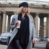 Junge, Hüfte und attraktives blondes Gehen um die Stadt mit Kaffee zum Mitnehmen, Mädchen in einem stilvollen Hut und ein grauer  Lizenzfreies Stockfoto