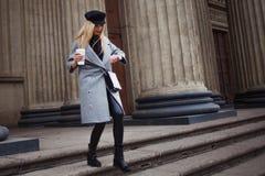 Junge, Hüfte und das attraktive blonde Gehen um die Stadt mit Kaffee zum Mitnehmen, betrachtet Uhr und beeilt sich auf Geschäft Lizenzfreie Stockfotos