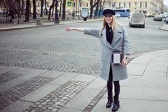 Junge, Hüfte und das attraktive blonde Hageln fahren, Mädchen in einem stilvollen Hut und ein grauer Mantel mit einem Taxi Lizenzfreie Stockfotografie
