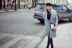 Junge, Hüfte und das attraktive blonde Hageln fahren, Mädchen in einem stilvollen Hut und ein grauer Mantel mit einem Taxi Stockfoto