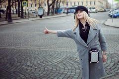 Junge, Hüfte und das attraktive blonde Hageln fahren, Mädchen in einem stilvollen Hut und ein grauer Mantel mit einem Taxi Stockfotos