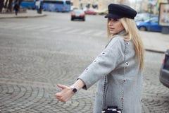 Junge, Hüfte und das attraktive blonde Hageln fahren, Mädchen in einem stilvollen Hut und ein grauer Mantel mit einem Taxi Stockbilder