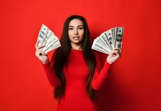 Junge h?bsche Frau im roten Kleid, das hinter B?ndel Geldbanknoten sich versteckt lizenzfreie stockbilder