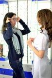 Junge h?bsche Frau versucht Augengl?ser an an einem Eyeweargesch?ft mithilfe eines Verk?ufers stockfoto