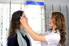 Junge h?bsche Frau versucht Augengl?ser an an einem Eyeweargesch?ft mithilfe eines Verk?ufers und der Aktien am Social Media unte lizenzfreie stockfotos