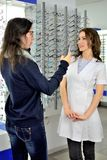 Junge h?bsche Frau versucht Augengl?ser an an einem Eyeweargesch?ft mithilfe eines Verk?ufers und der Aktien am Social Media unte stockbild
