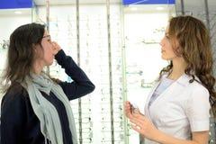 Junge h?bsche Frau versucht Augengl?ser an an einem Eyeweargesch?ft mithilfe eines Verk?ufers und der Aktien am Social Media unte stockfotos