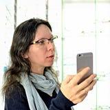 Junge h?bsche Frau versucht Augengl?ser an an einem Eyeweargesch?ft mithilfe eines Verk?ufers und der Aktien am Social Media unte lizenzfreies stockfoto