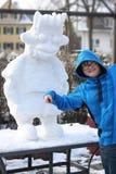 Junge haben Spaß mit einem Schneemann Lizenzfreie Stockbilder