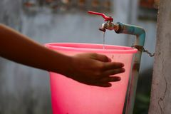 Junge Hand, die Wasser mit einem Plastikeimer von einem alten langsam fließenden Wasserhahn mit großer Geduld sammelt - Wasserk stockfoto