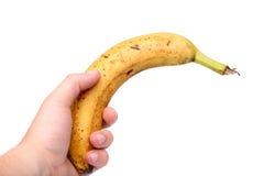 Junge Hand und alte Banane Stockfoto