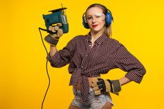 Junge Handwerkerin mit einer Laubsäge vor gelbem Hintergrund lizenzfreie stockfotos