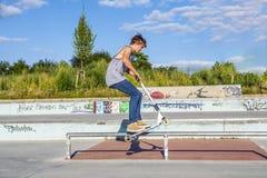 Junge hat den Spaß, der mit seinem Roller springt Stockfotografie