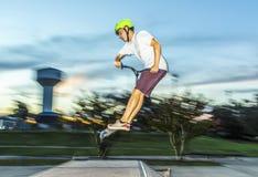 Junge hat den Spaß, der seinen Stoßroller am Rochenpark reitet Lizenzfreie Stockbilder