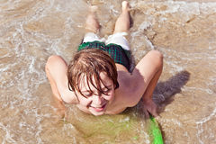 Junge hat Spaß mit dem Surfbrett Stockfoto