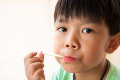Junge hat zufrieden gestellt, wann er Lieblingseiscreme isst Lizenzfreie Stockfotografie