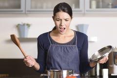 Junge Hausfrau, die ein Unglück in der Küche hat Stockfotografie