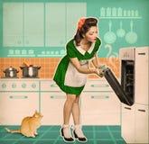 Junge Hausfrau, die in einem Ofen kocht Retro- Küchenrauminnenraum lizenzfreies stockbild